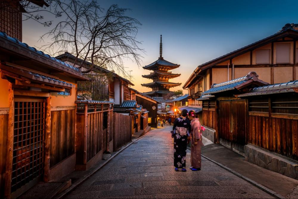 Photo of two geisha women walking through a Japanese village