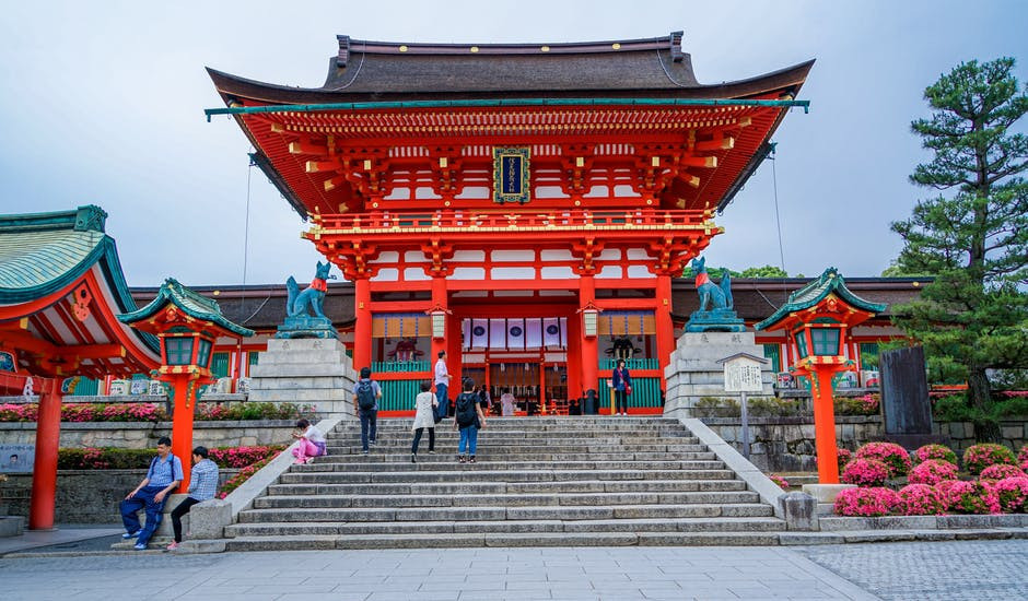 Image of people walking up stairs into a Japanese Temple