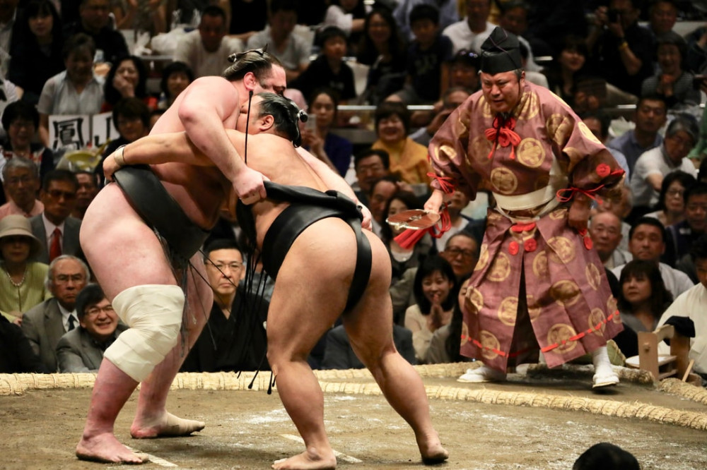Sumo Wrestlers competing in front of a crowd