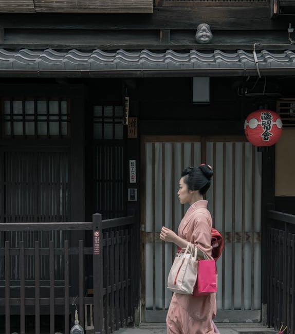 Woman in traditional clothing walking down a street in Japan