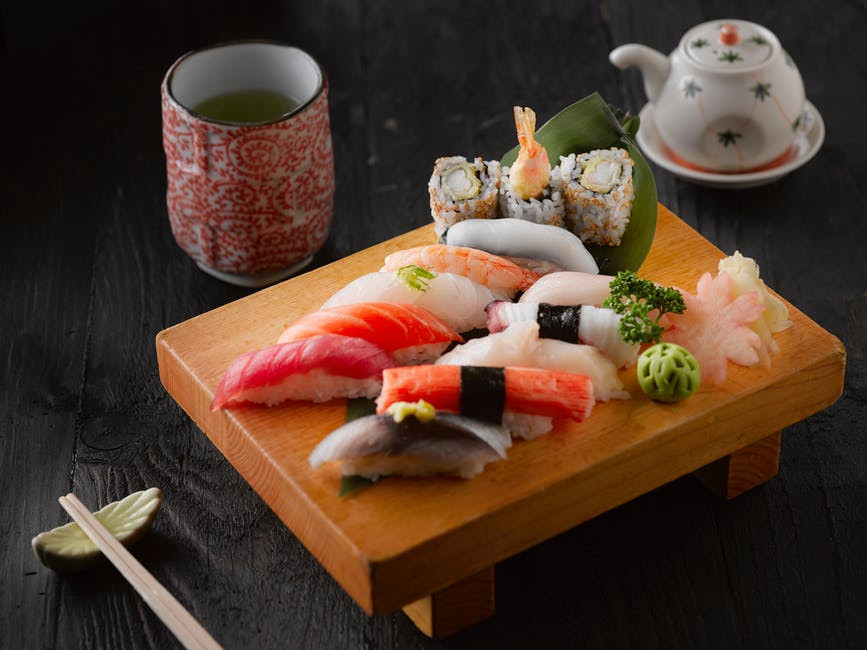 Wooden plate with sushi and matcha green tea