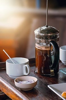 Image of a French Coffee Press next to an empty cup and bowl of sugar